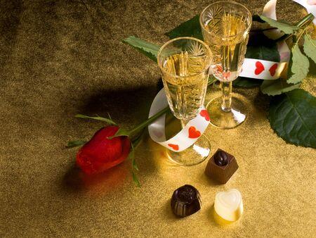 Brille mit Wein und rote rose mit einem gold Hintergrund Lizenzfreie Bilder