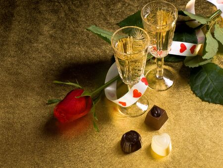 glasses with wine and red  rose on a gold background Stock Photo - 6245672