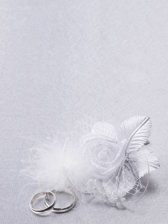 Two silver weddings rings and floral  decoration
