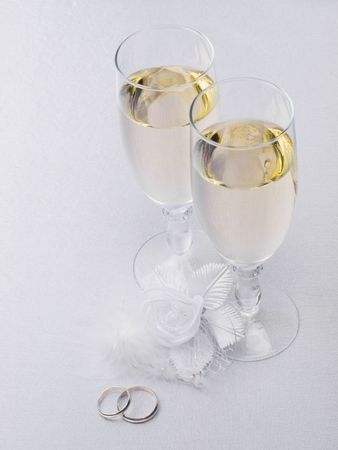 Two glasses with champagne and wedding decoration on white silk