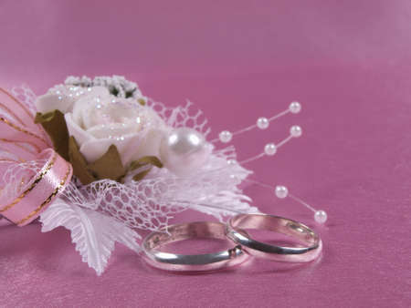 Weddings accessories are a buttonhole and rings on a pink background photo