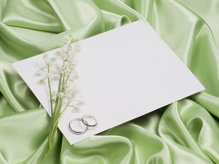 Silver wedding rings, card  and lily of the valley green  background photo