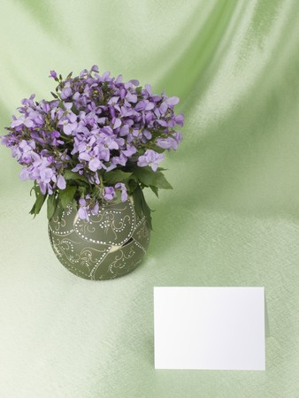 flowers are in a vase and empty memo card with space for your own text, over  green background photo