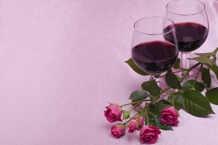 two glass with wine and roses on a pink  background photo