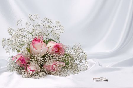 Bouquet  roses and weddings rings on a background white silk photo