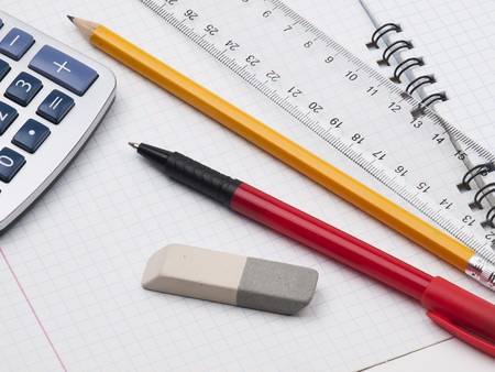 protractor, pen, pencil, rules, calculator and workbook page  photo