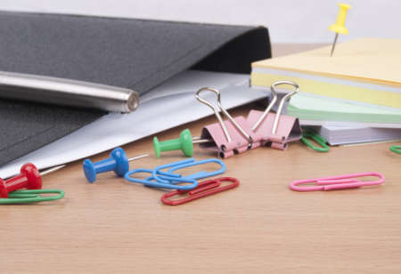 Stationeries on a table. Pen,  marker, paper clip. photo