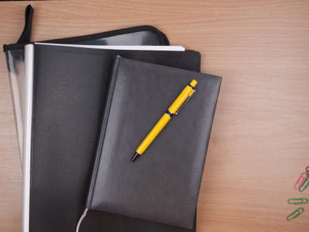 business diary, black folder and yellow pen  photo