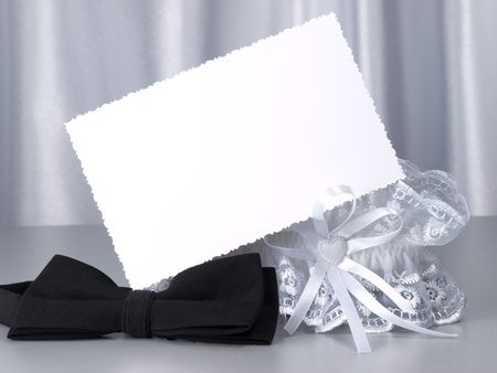 Card, bridal garter and bow  on a background white silk Stock Photo - 8513807