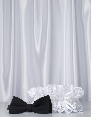 bridal garter and bow  on a background white silk Stock Photo - 8561311
