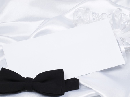 Card, bridal garter and bow  on a background white silk Stock Photo - 8561313