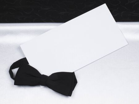 Card,  bow tie  on a background black and white silk