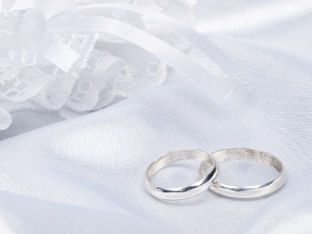 Background from white silk with a lace and rings Stock Photo