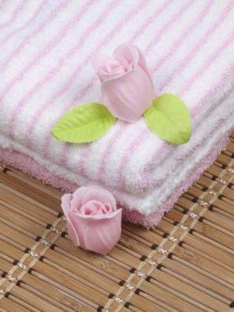 convolute: Convolute towels and soap as a flower of rose on a serviette from a bamboo