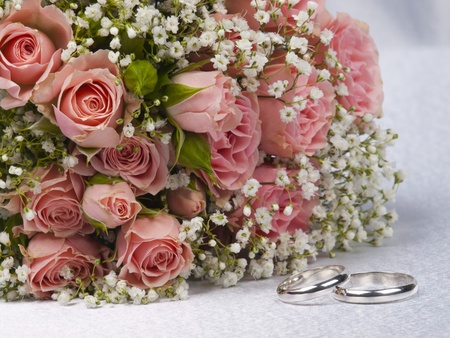 Bouquet Rosen und Hochzeiten Ringe auf Hintergrund wei�er Seide Lizenzfreie Bilder