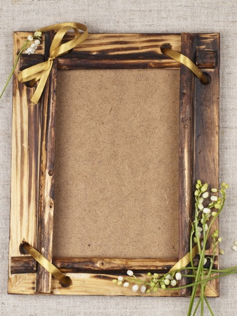 Old wooden frame for a picture with the lilies of the valley Stock Photo