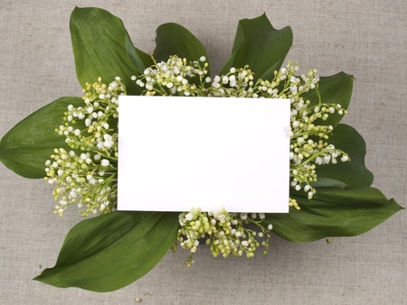 Card for congratulation  and lily of the valley on a background from a canvas