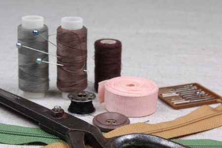 Sewing kit. Scissors, bobbins,  needles on the  fabric.  photo