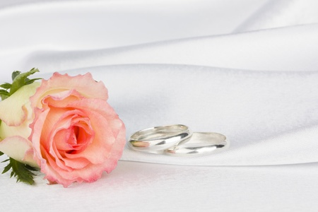 Rose and weddings rings on a background white silk Stock Photo - 9959475
