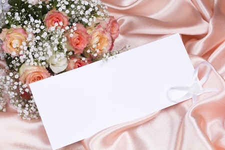Beautiful roses and card for your text on a background pink silk photo