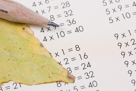 multiplicaci�n: tabla de multiplicar, las hojas de oto�o amarillas y l�piz Foto de archivo