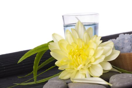 plainness: Sea smooth stones,  bath salt and yellow flower Stock Photo