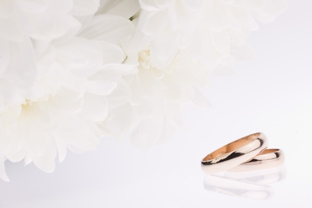 White flowers and gold wedding rings photo