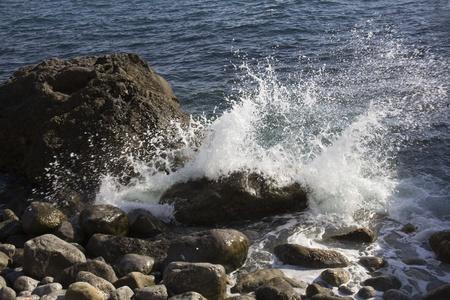 Sea wave breaks on the rocks photo