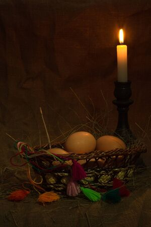 easter candle is burning: Eggs in a basket on a dark background