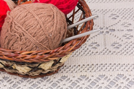 dense mats: knitting needles and skein of brown wool