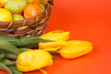 Easter eggs in a basket on a orange  background photo
