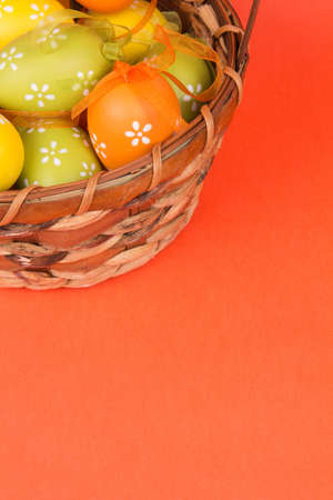 Easter eggs in a basket on an orange background photo