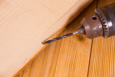The old electric drill and wooden planks photo