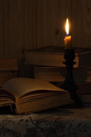 Altes Buch und eine Kerze auf dem Tisch Lizenzfreie Bilder