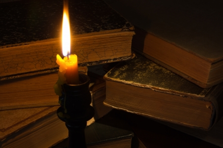 Old book and a candle on the table photo