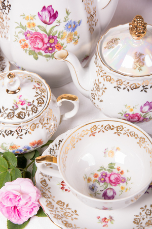 tea set: Antique floral tea set on a white tablecloth