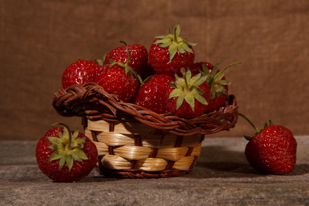 strawberries in a basket on old wooden background photo