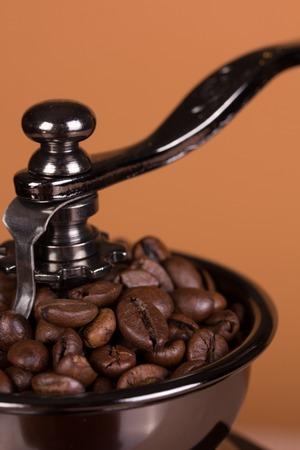 Vintage manual coffee grinder on a brown background photo