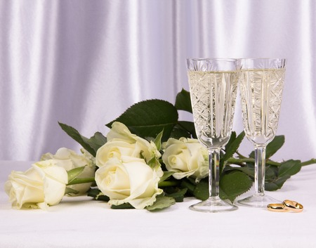Two glass with wine and rose on a white background