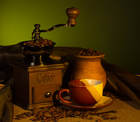 Vintage coffee grinder, cup with a drink and a pitcher with roasted beans photo