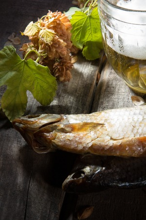 Mug of beer and dried fish on old wooden board Stock Photo