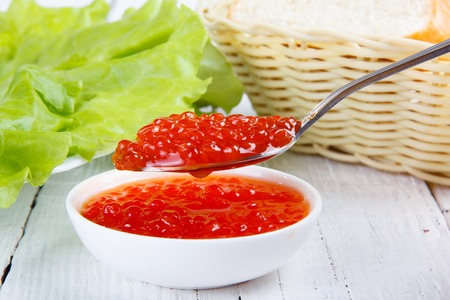 fresh delicious  red caviar  on an old wooden table photo