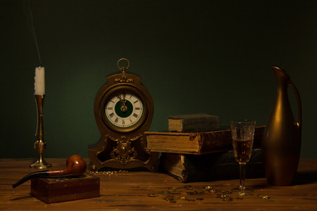 Still life with old books, vintage clock, candle and jug