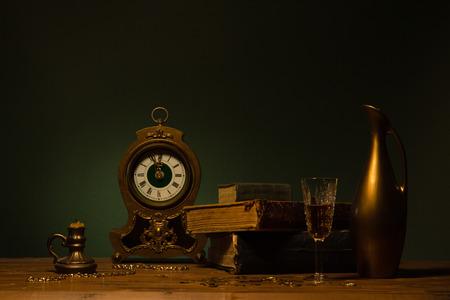 古書、ヴィンテージ時計、キャンドル、水差しのある静物