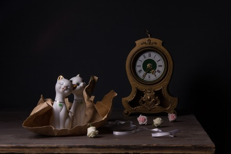 Still life with porcelain figurines and vintage clock