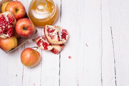 조각 잘 익은 석류, 꿀, 사과 흰 나무 배경에