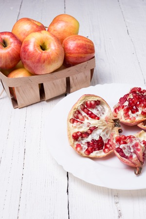 作品熟したザクロと木製の白い背景の上のリンゴ