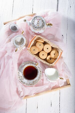 sugar veil: Morning tea concept with cup of tea, milk and biscuit Stock Photo