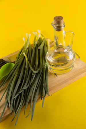 cooking oil: Fresh green onion on a cutting board