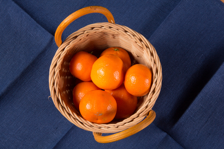 Tangerines or oranges, mandarins, clementines, citrus fruits on a blue linen napkin Stock Photo